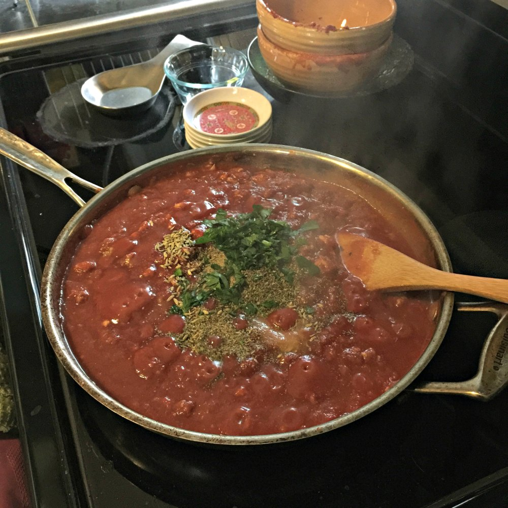 Adding the herbs and spices to the sauce.